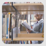 Student in school uniform looks at a book in a square sticker