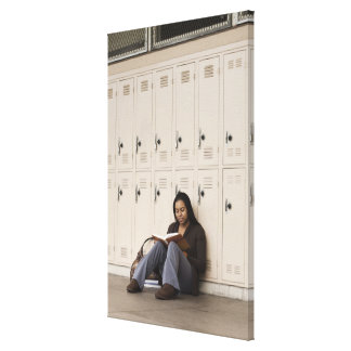Student leaning on school lockers studying canvas print