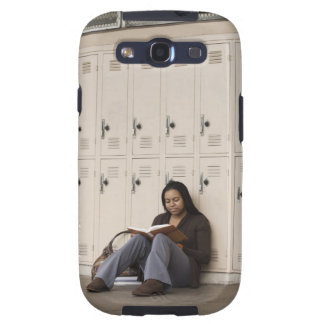 Student leaning on school lockers studying galaxy s3 case