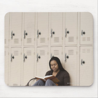 Student leaning on school lockers studying mouse pad