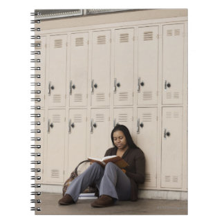Student leaning on school lockers studying notebooks