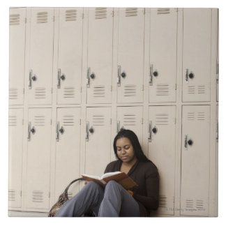 Student leaning on school lockers studying tile