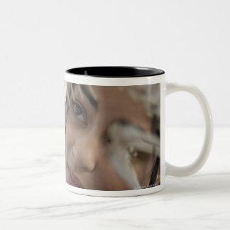 Student looking at animal skeleton Two-Tone coffee mug