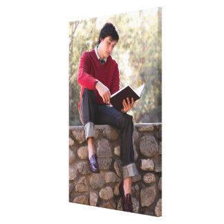 Student Reading Book and Sitting on Stone Wall Canvas Print