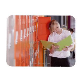 Student removing binder from school locker magnet