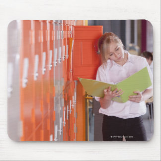 Student removing binder from school locker mouse pad
