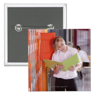 Student removing binder from school locker pinback button