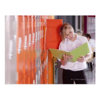 Student removing binder from school locker postcard