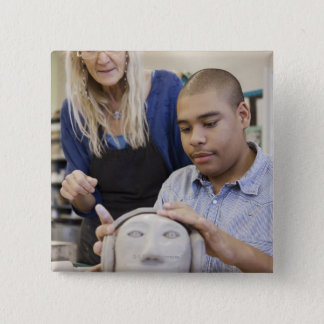 Student sculpting bust in classroom button