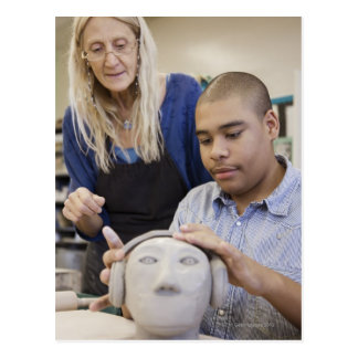 Student sculpting bust in classroom postcard