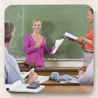 Student talking to class and standing by teacher beverage coaster