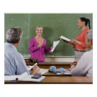 Student talking to class and standing by teacher poster