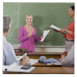Student talking to class and standing by teacher tile