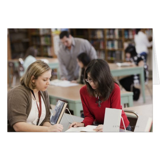 Student talking to librarian in school library card