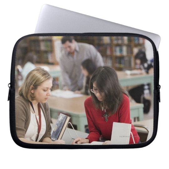 Student talking to librarian in school library computer sleeve