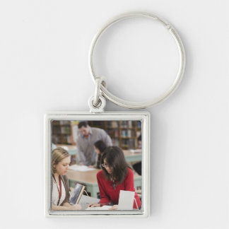 Student talking to librarian in school library key chains