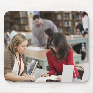 Student talking to librarian in school library mouse pad