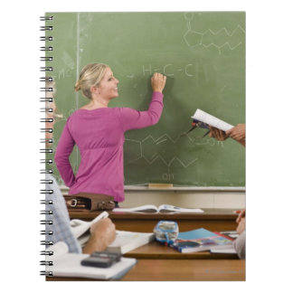 Students and teacher in classroom notebook