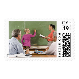 Students and teacher in classroom postage stamp