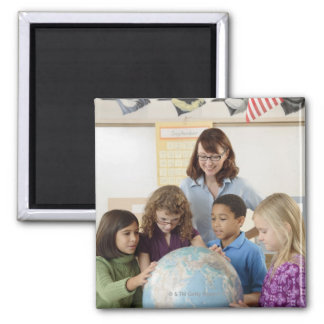 students and teacher with globe magnet