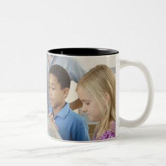 students and teacher with globe Two-Tone coffee mug