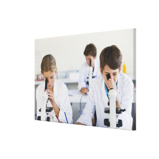 Students looking through microscopes canvas print