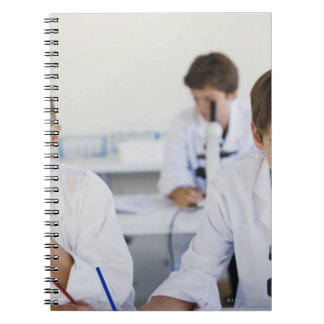 Students looking through microscopes notebook