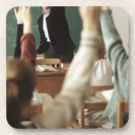 Students raising their hands in classroom coaster