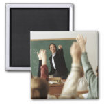 Students raising their hands in classroom fridge magnet