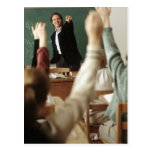 Students raising their hands in classroom post card