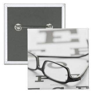 Studio shot of eyeglasses on eye chart 2 inch square button