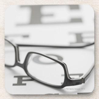 Studio shot of eyeglasses on eye chart beverage coaster