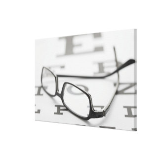 Studio shot of eyeglasses on eye chart canvas print