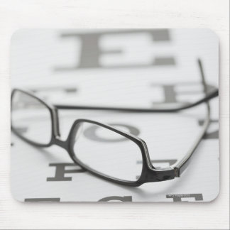Studio shot of eyeglasses on eye chart mouse pad