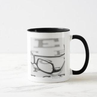 Studio shot of eyeglasses on eye chart mug