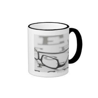Studio shot of eyeglasses on eye chart coffee mug
