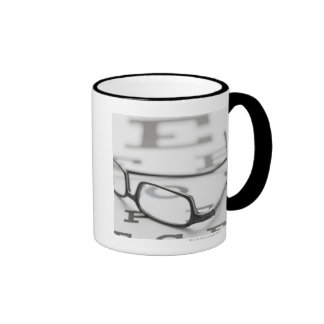 Studio shot of eyeglasses on eye chart ringer coffee mug