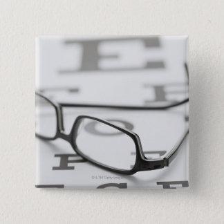 Studio shot of eyeglasses on eye chart pinback button