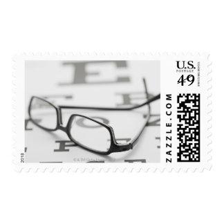 Studio shot of eyeglasses on eye chart postage stamp