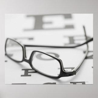 Studio shot of eyeglasses on eye chart poster