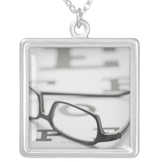 Studio shot of eyeglasses on eye chart silver plated necklace