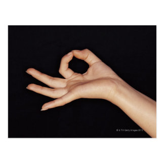 Studio shot of hand gesturing a sign postcard