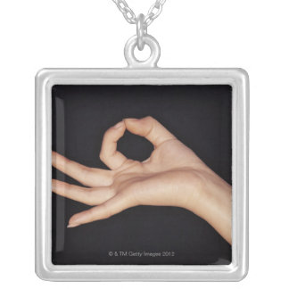 Studio shot of hand gesturing a sign square pendant necklace