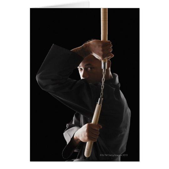 Studio shot of man exercising with nunchaku card