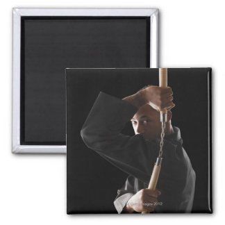 Studio shot of man exercising with nunchaku magnet