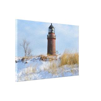 Sturdy Lighthouse on a Rocky Coast in Winter Canvas Print
