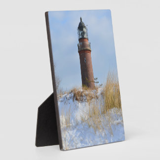 Sturdy Lighthouse on a Rocky Coast in Winter Plaque