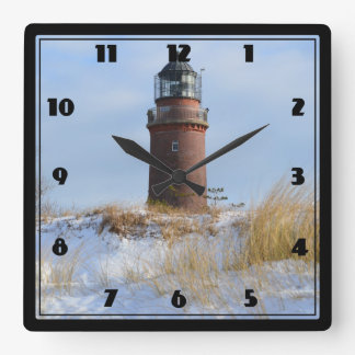 Sturdy Lighthouse on a Rocky Coast in Winter Square Wall Clock