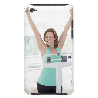 Successful weight loss. Happy woman weighing Barely There iPod Cover