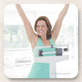 Successful weight loss. Happy woman weighing Beverage Coaster
